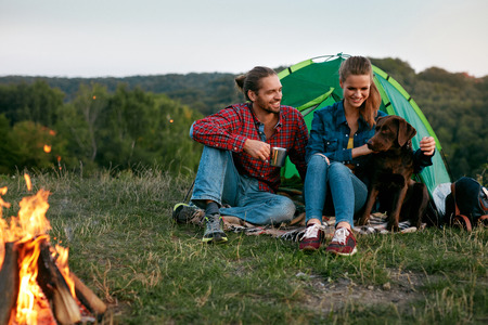 Smiling Young People Sitting Near Camping Tent And Playing With Pet, Traveling On Weekend. High Quality Image 写真素材