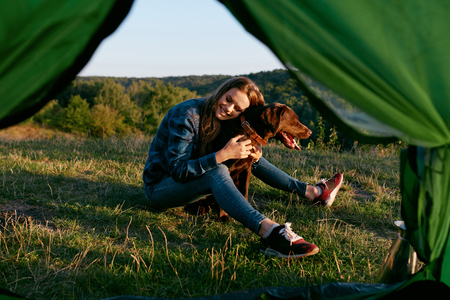 Beautiful Smiling Girl Playing With Pet, Sitting Near Tent On Grass And Enjoying Summer. Travel Concept. High Quality Image. Banco de Imagens - 94715078