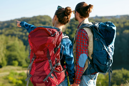 Back View Of Young Man And Woman With Bright Colorful Backpacks Hiking In Mountains, Having Trip On Summer Vacation. High Quality Image