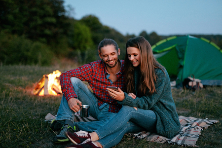 Portrait Of Young Lovely People Looking At Mobile Phone While Having Romantic Getaways. Couples Vacations. High Resolution. 写真素材
