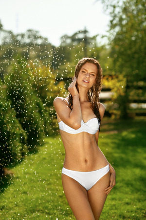 Fashion Woman In Bikini With Sexy Body Enjoying Summer. Beautiful Hot Girl With Fit Body, Healthy Tan Skin And Wet Hair In White Stylish Swimwear Relaxing Under Falling Water In Garden. High Quality