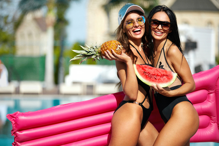 Summer Fashion. Girls In Swimsuits Having Fun Near Pool On Vacation. Sexy Female Models In Trendy Sunglasses And Fashionable Swimwear With Tanned Bodies, Air Mattress And Fruits. High Quality Image. Stok Fotoğraf - 95293387
