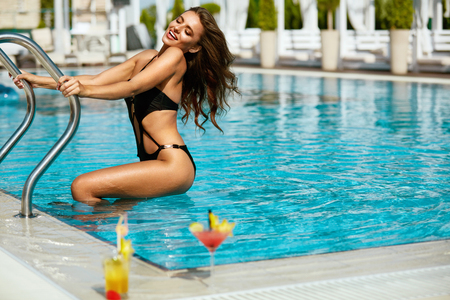 Pool Fashion. Woman In Pool In Summer. Beautiful Girl In Fashionable Swimwear On Hot Sexy Body Coming Out From Pool. Female Enjoying Summer Travel In Swimming Pool At Luxury Resort. High Resolution.