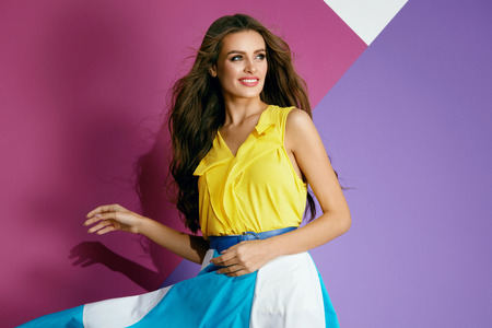 Fashion Clothes. Beautiful Woman In Colorful Dress In Summer. Fashionable Smiling Girl In Stylish Yellow Blouse And Trendy Colorful Skirt On Violet Background. Female Summer Style. High Quality
