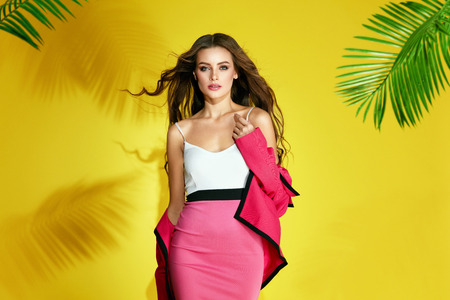 Summer Fashion. Happy Young Female Model In Summer Clothes. Beautiful Stylish Woman In Sexy Colorful Pink Dress With Elegant Hairstyle And Makeup On Yellow Background. Summer Look. High Quality Stock Photo