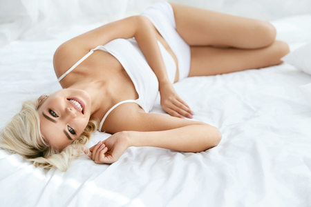 Beautiful Smiling Woman With Blond Hair And Beauty Face. Portrait Of Happy Blonde Girl With Slim Fit Body, With Natural Hairstyle And Makeup Wearing White Underwear In Light Interior. High Quality Stock Photo