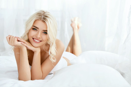 Schöne glückliche Frau auf Bett im hellen Innenraum. Attraktive glückliche junge Frau mit dem blonden Haar, gesunder glatter weicher Haut und natürlichem Gesichtsmake-up, die auf weißer Bettwäsche liegen. Hautpflege. Hohe Qualität