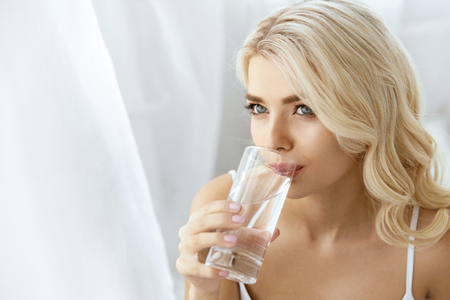 Drinking Water. Woman With Glass Of Water. Portrait Of Beautiful Happy Female Drinking Clean Water In Light Interior. Healthy Diet Concept. High Quality Image.