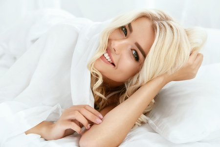 Happy Woman With Beautiful Face Smiling, Lying On Bed. Portrait Of Beautiful Young Female With Healthy Blonde Hair, Fresh Soft Facial Skin And Perfect White Smile On White Bedding. High Resolution.