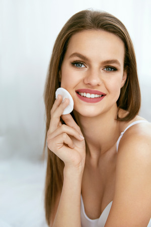 Clean Face Skin. Young Woman Removing Makeup. Beautiful Smiling Female Using Cosmetic White Cotton Pad For Cleaning Facial Skin From Cosmetics. Skin Care. High Quality Image