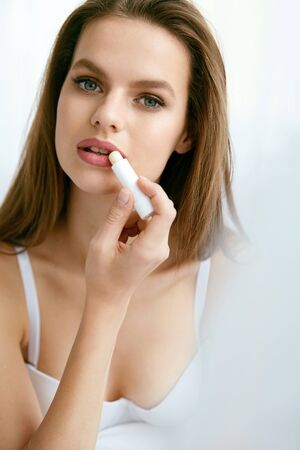 Lips Skin Care. Female Applying Hygienic Lip Balm. Portrait Of Beautiful Woman With Beauty Face And Healthy Soft Smooth Skin Putting Hygienic Lipstick. Lips Protection. High Resolution.