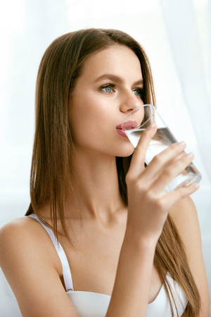 Drink Water. Young Woman With Glass Of Water. Portrait Of Beautiful Healthy Girl With Beauty Face Drinking Fresh Pure Water In Morning. Diet Concept. High Quality Image. Stock Photo