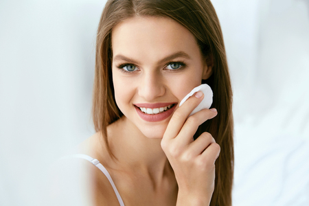 Woman Cleaning Face With White Pad. Beautiful Girl Removing Makeup White Cosmetic Cotton Pad. Happy Smiling Female Taking Off Makeup From Facial Skin With Cosmetic Pad. Face Skin Care. High Quality