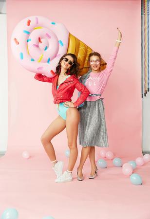 ファッション女性。夏服で幸せな友人。カラフルな背景に大きなインフレータブルアイスクリームを室内に保持し、楽しさと笑いを持ってスタイリ