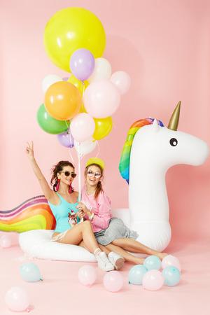 Chicas de moda de verano divirtiéndose con globos en flotador de unicornio. Hermosas mujeres sonrientes en ropa de moda y trajes de baño con globos de colores sobre fondo rosa. Estilo de mujer Imagen de alta calidad. Foto de archivo