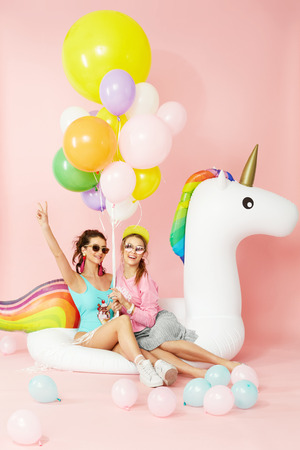 Summer Fashion Girls Having Fun With Balloons On Unicorn Float. Beautiful Smiling Women In Fashionable Clothes And Swimwear With Colorful Balloons On Pink Background. Women Style. High Quality Image. Фото со стока