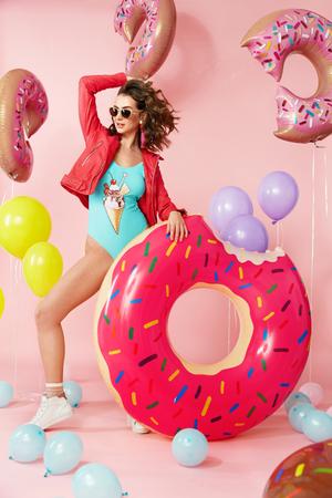 夏のファッション。風船で水着を着た女性。ピンクのバクグラウンドにインフレータブルドーナツフロートとファッショナブルなカラフルな水着で 写真素材