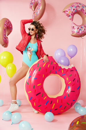 Summer Fashion. Woman In Swimsuit With Balloons. Beautiful Happy Young Female Model With Fit Body In Fashionable Colorful Swimwear With Inflatable Donut Floats On Pink Bakcground. High Resolution. Stockfoto