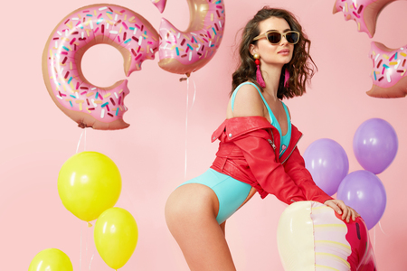 Woman In Summer. Fashion Model in Swimsuit And Sunglasses. Beautiful Smiling Female With Sexy Body In Fashionable Sunglasses, Trendy Swimwear Having Fun With Floats And Balloons Indoors. High Quality