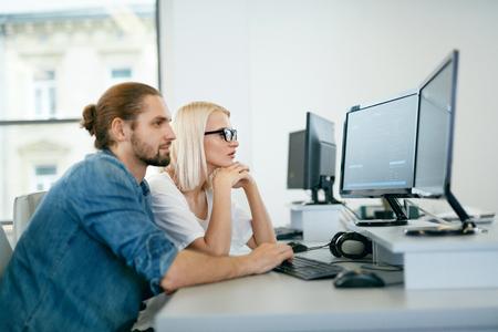 Équipe informatique travaillant au bureau. Programmation de personnes sur ordinateur. Jeunes programmeurs tapant le code de données sur le clavier au lieu de travail, en regardant les écrans d'ordinateur dans un bureau moderne. Haute qualité