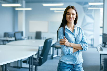 Woman In Office. Female At Work In Light Modern IT Office. Portrait Of Beautiful Smiling Young Worker In Casual Clothes With Arms Crossed At Workplace. Business Person, People At Work. High Quality Stockfoto