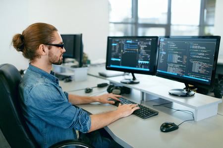 Programmierung. Bemannen Sie das Arbeiten an Computer in IT-Büro und am Schreibtisch sitzen, der Codes schreibt. Programmierer-Typing Data Code, arbeitend an Projekt in der Software-Entwicklungsfirma. Hochwertiges Bild.