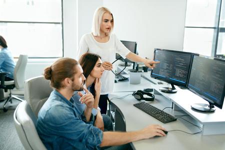 IT-Büro. Leute, die am offenen Arbeitsplatz arbeiten. Gruppe Programmierer, die zusammen an dem Projekt, programmierend auf Computer im modernen hellen Büro arbeiten. Arbeit in IT-Unternehmen. Hohe Auflösung