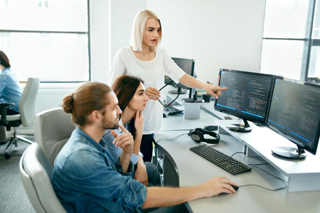 IT office. People Working At Open Workplace. Group Of Programmers Working Together On Project, Programming On Computer In Modern Light Office. Work In IT Company. High Resolution Stockfoto