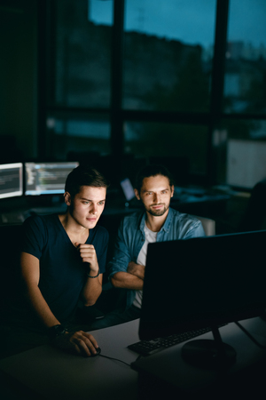 Programmers Working, Looking At Computer In Office. Handsome Young Men In Casual Closes Typing Codes, Working On Computer While Sitting At Workplace In Evening. High Quality Image. Stock Photo