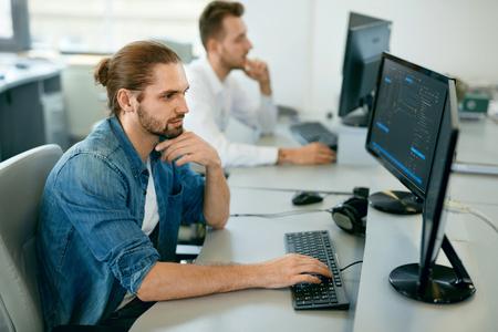 Programadores trabajando, mirando la computadora en la oficina de TI. Hombres jóvenes guapos en casual cierra códigos de mecanografía, trabajando en la computadora mientras está sentado en el lugar de trabajo. Imagen de alta calidad.