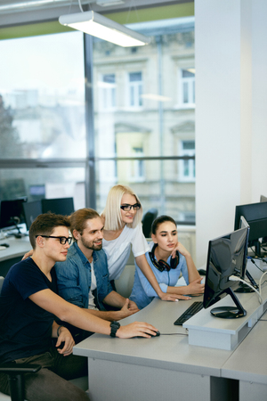 Team Working In Office. People Working On Project. Young Beautiful Programmers Typing Data Code On Keyboard At Workplace, Looking At Computer Monitors In Modern Office. High Quality Image.