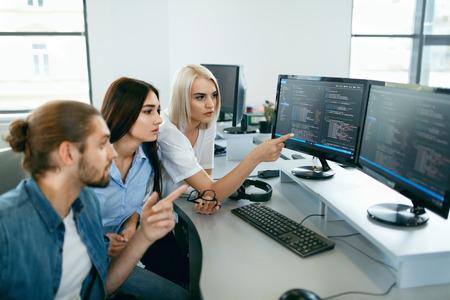IT-Büro. Leute, die am offenen Arbeitsplatz arbeiten. Gruppe Programmierer, die zusammen an dem Projekt, programmierend auf Computer im modernen hellen Büro arbeiten. Arbeit in IT-Unternehmen. Hohe Auflösung Standard-Bild