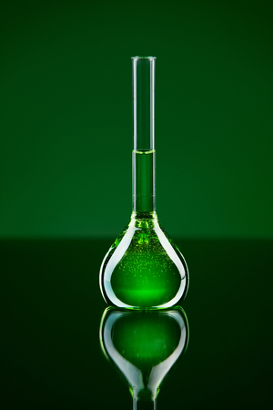 Laboratory Supplies. Glass With Chemical Liquid. Close Up Of Transparent Flask With Green Fluid On Table On Green Background. Glassware Instruments. High Resolution.