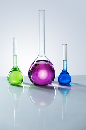 Laboratory Supplies. Colorful Glass With Chemical Liquid. Close Up Of Transparent Flasks With Green, Blue And Purple Fluid On Table. Glassware Instruments. High Resolution.