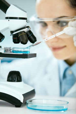 Medical Analysis. Female Scientist Doing Test In Laboratory. Close Up Of Young Woman Doctor In Medicine Glasses Using Microscope, Researching, Working In Light Modern Laboratory Clinic. High Quality