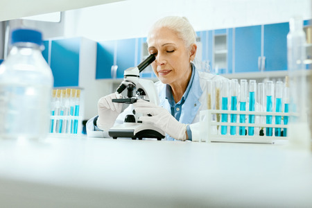 Laboratory Research. Woman Looking Through Microscope. Portrait Of Female Scientist In White Coat Working At Workplace In Modern Light Laboratory. Clinical Laboratory. High Quality Image.