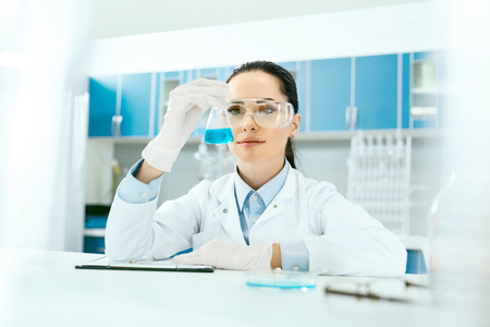 Scientific Laboratory. Female Scientist With Laboratory Glass. Portrait Of Beautiful Woman In Glasses Holding Glassware With Liquid In Hand, Looking At Chemical Reaction At Workplace. High Resolution.
