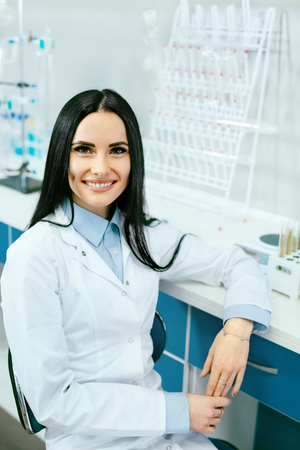 Scientist In Laboratory. Female Doctor At Work. Portrait Of Happy Young Beautiful Woman In White Laboratory Coat Near Workplace In Light Modern Laboratory. Medical Staff. High Quality