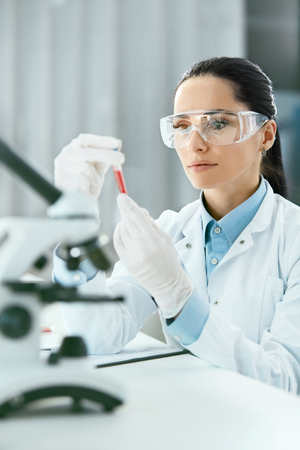 Laboratory. Woman Doing Medical Research With Blood. Portrait Of Beautiful Young Female In White Coat Sitting At Workplace And Working With Blood Sample In Lab. Medical Laboratory. High Resolution