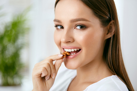 Woman Eating Healthy Diet Food In Kitchen Stock Photo