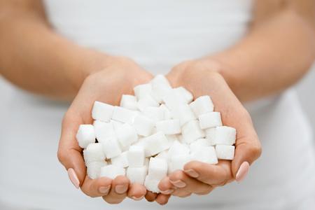 砂糖キューブと女性の手。白砂糖で女性の手を閉じます。高品質 写真素材