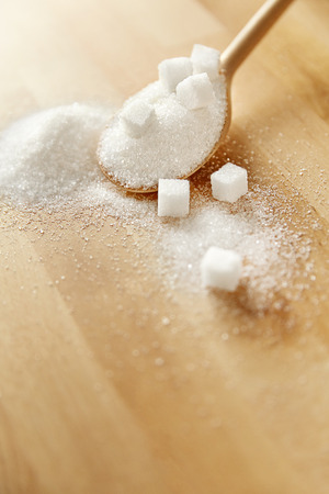Close Up Of White Sugar In Spoon On Table. Sugar Cubes And Granulated Sugar Lying On Wooden Table. High Quality Image.