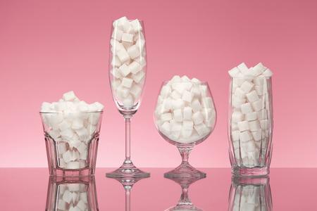Suiker In Dranken. Glazen Vol Witte Suikerklontjes. Sluit omhoog van Transparante Glasswear met Geraffineerde Suiker op Roze Achtergrond. Hoge kwaliteit