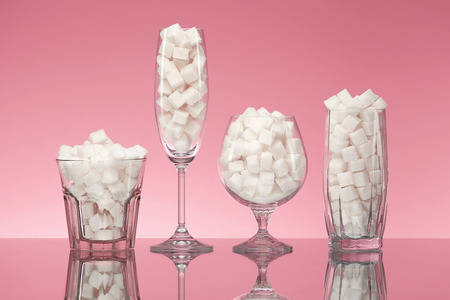 Sugar In Drinks. Glasses Full Of White Sugar Cubes. Close Up Of Transparent Glasswear With Refined Sugar On Pink Background. High Quality