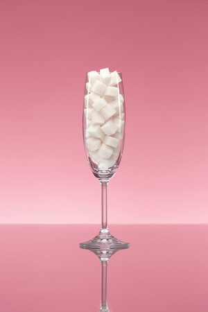 Sugar In Drinks. Glass Full Of White Sugar Cubes. Close Up Of Transparent Glass With Refined Sugar On Pink Background. High Quality Imagens