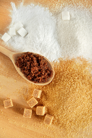 Sugar. White Sugar And Brown Sugar On Wood Background. Close Up Of Sugar Cubes And Granulated Sugar In Spoon Lying On Wooden Table. High Quality Image.