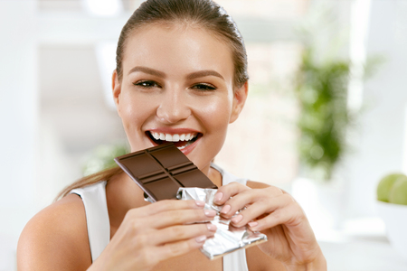 Frau, die Schokolade isst. Schönes Mädchen mit Süßigkeiten. Porträt der glücklichen lächelnden jungen Frau, die zuhause Schokolade beißt und genießt Lebensmittel und Diät-Konzept. Hohe Qualität
