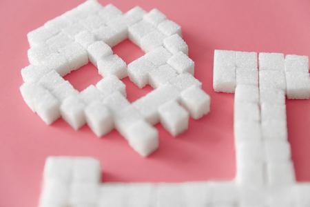 頭蓋骨の形で白い砂糖キューブ。ピンクの背景に洗練された砂糖のクローズアップ。致命的な砂糖中毒。糖尿病と死の概念。高品質