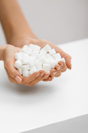 Female Hands With Sugar Cubes. Close Up Of Womans Hands With White Sugar. High Quality
