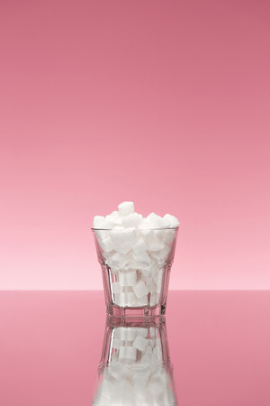 Sugar In Drinks. Glass Full Of White Sugar Cubes. Close Up Of Transparent Glass With Refined Sugar On Pink Background. High Quality Stock Photo